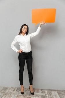 Bild der geschäftsfrau in voller länge, die formelles outfit trägt, das leere copyspace-blase für ihren text hält und auf kamera lächelt, lokalisiert über grauem hintergrund