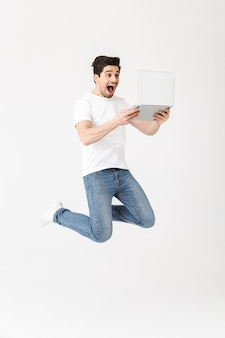 Bild der glücklichen aufgeregten jungen mannaufstellung lokalisiert über weißer wand unter verwendung des laptopcomputerspringens.