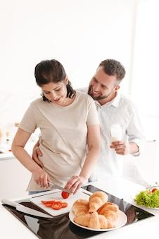 Bild der glücklichen familie frau und ehemann 30er jahre kochen und frühstück in der küche zu hause vorbereiten