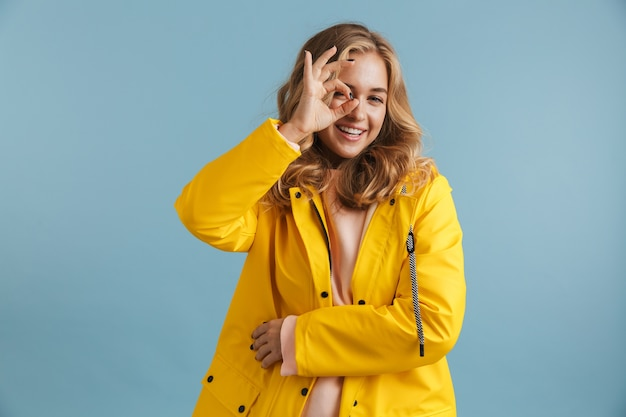Bild der glücklichen frau 20s, die gelben regenmantel zeigt ok zeichen