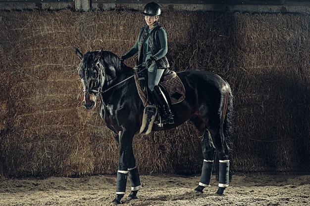 Bild der glücklichen frau, die auf reinrassigem pferd sitzt