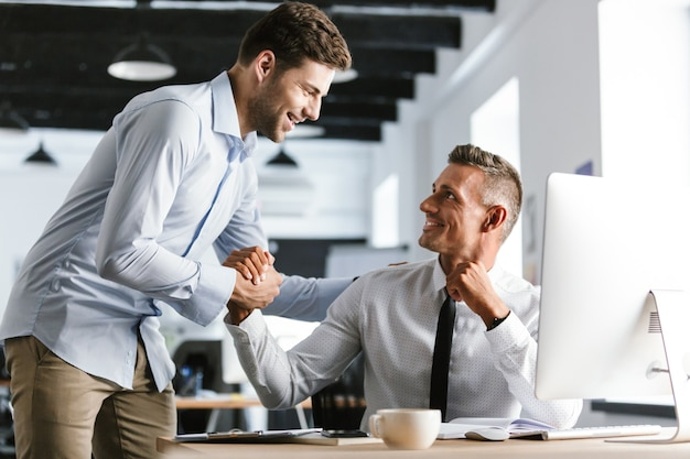 Bild der glücklichen geschäftsmannmitarbeiter 30s in der formellen kleidung, die im büro arbeitet und hände zusammen schüttelt