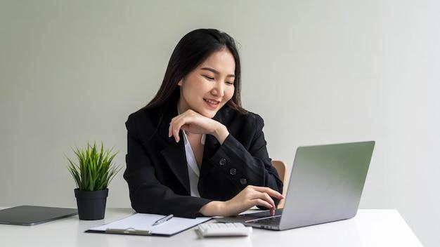 Bild der glücklichen lächelnden asiatischen geschäftsfrau, die an ihrem laptop im büro arbeitet.