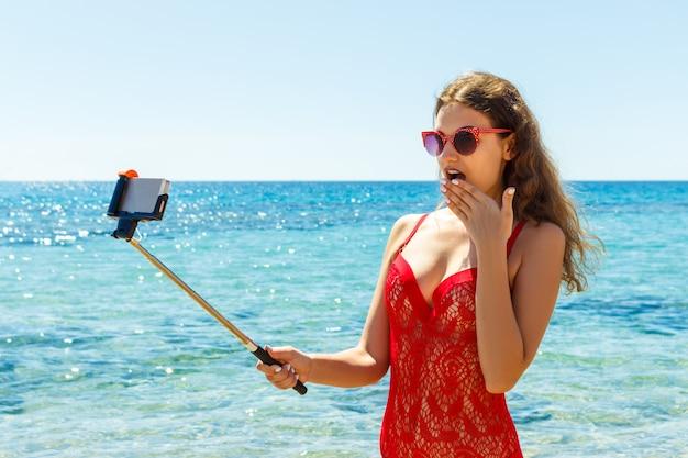 Bild der glücklichen lächelnden frau, die telefonkamera verwendet und selfie macht