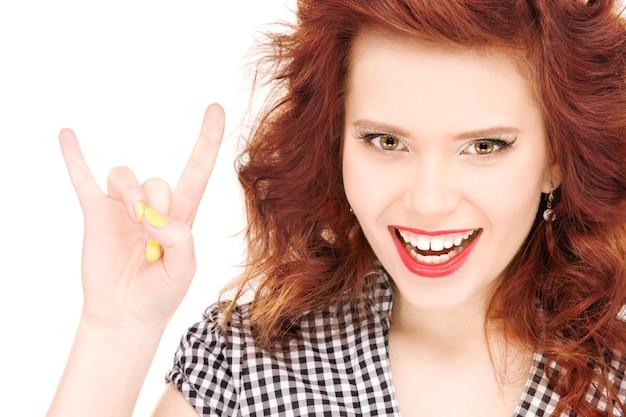 Bild der glücklichen teenagerin, die teufelshörnergeste zeigt