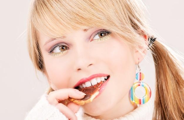 Bild der glücklichen teenagerin mit keks