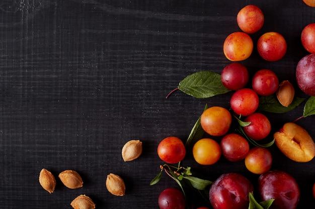 Bild der gruppe von früchten - pflaumen und apriches auf der oberfläche des dunklen tisches. bild mit speicherplatz für ihren werbe- oder promotiontext. konzept für gesunde ernährung. köstliche frucht auf schwarzem hintergrund.