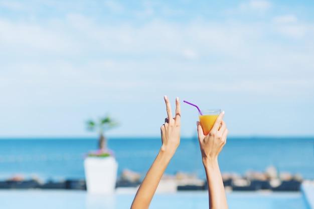 Bild der hände des mädchens, das cocktail auf dem seehintergrund hält. es sieht cool aus.
