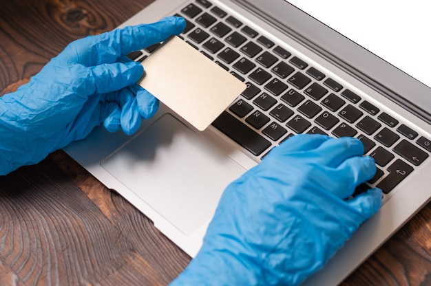 Bild der hände in den medizinischen handschuhen, die eine kreditkarte halten und auf einem laptop tippen.