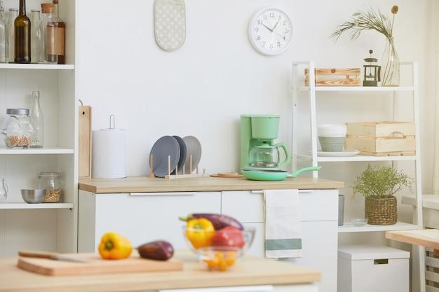 Bild der häuslichen modernen küche mit küchentisch mit gemüse auf ihm im haus