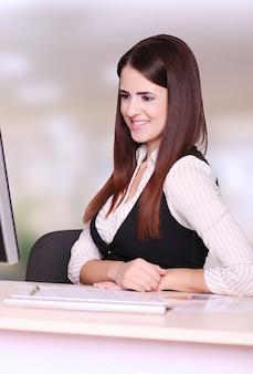 Bild der hübschen geschäftsfrau, die vor computer sitzt und seinen schirm betrachtet