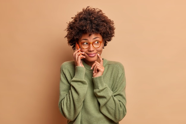Bild der hübschen lächelnden frau spricht auf dem handy mit freund besprechen pläne für wochenenden konzentriert beiseite glücklich hat intelligenter blick trägt transparente brille lässigen pullover