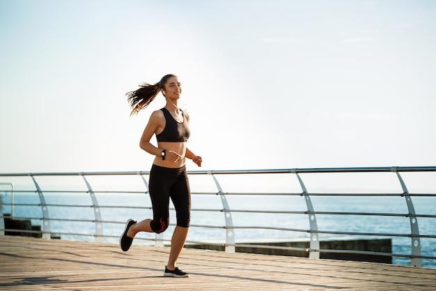Bild der jungen attraktiven fitnessfrau, die mit meer an der wand läuft