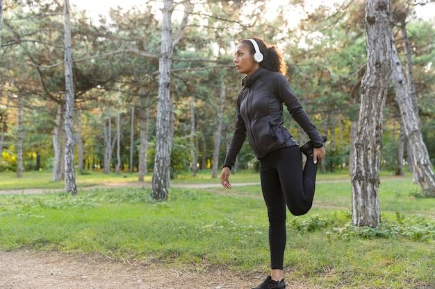 Bild der jungen frau 20s, die schwarzen trainingsanzug trägt, der sport macht und körper im grünen park streckt