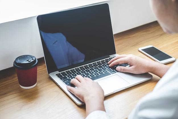 Bild der jungen frau arbeitend vor dem laptop, der schirm mit einem sauberen weißen schirm und einer leerstelle nach schreibinformationen des textes und der hand über tastatur im modernen arbeitsplatz betrachtet