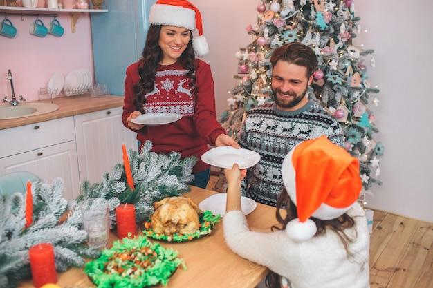 Bild der jungen frau dem mädchen platte gebend. sie versteht es. junger mann sieht seine tochter an und lächelt. es gibt festliches essen am tisch. die leute tragen weihnachtskleidung.