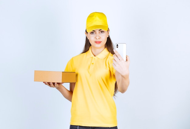 Bild der jungen frau, die paket hält und selfie über weißer wand nimmt.
