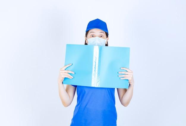Bild der jungen frau in medizinischer maske, die mit blauem ordner über weißer wand posiert.