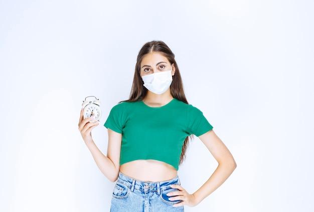 Bild der jungen frau in medizinischer maske, die mit wecker posiert.