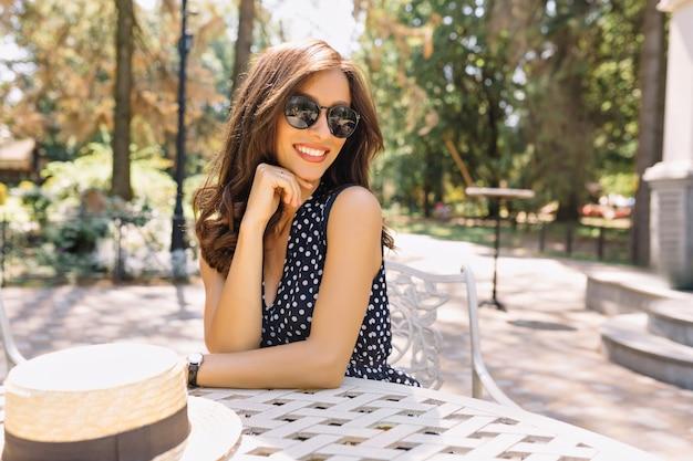 Bild der jungen frau mit schönen haaren und charmantem lächeln sitzt in der sommercafeteria im sonnenlicht. sie trägt ein hübsches sommerkleid und eine schwarze sonnenbrille.