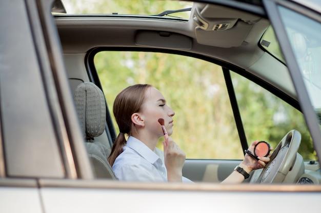 Bild der jungen geschäftsfrau, die make-up macht, während sie ein auto im stau fährt