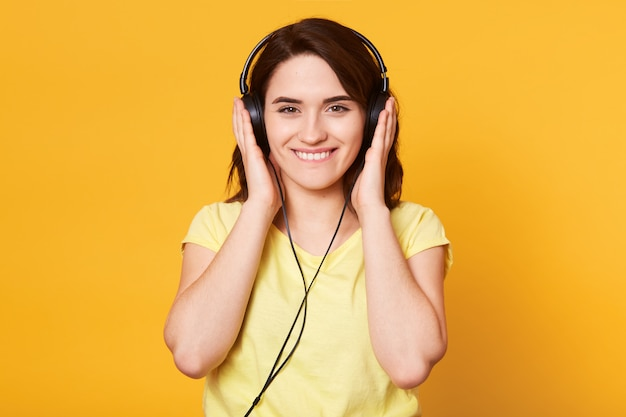 Bild der jungen glücklichen frau mit kopfhörern, die musik lokalisiert über gelb hören
