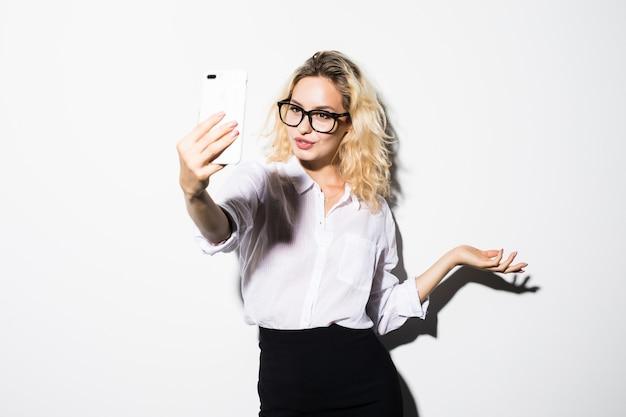 Bild der jungen glücklichen geschäftsfrau lokalisiert über weißem wandhintergrund, der beiseite schaut und per telefon mit freunden winkt.