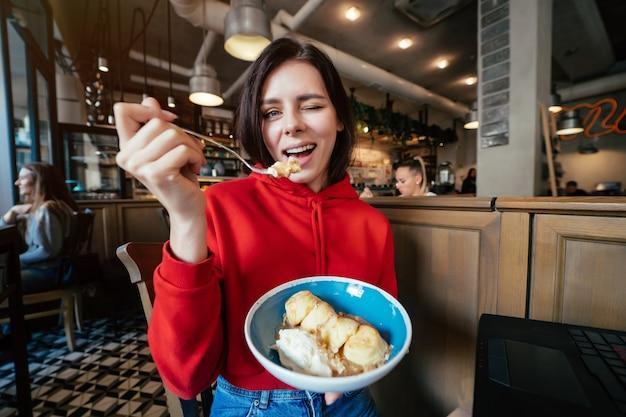 Bild der jungen glücklichen lächelnden frau, die spaß hat und eiscreme im kaffeehaus- oder restaurantnahaufnahmeporträt isst