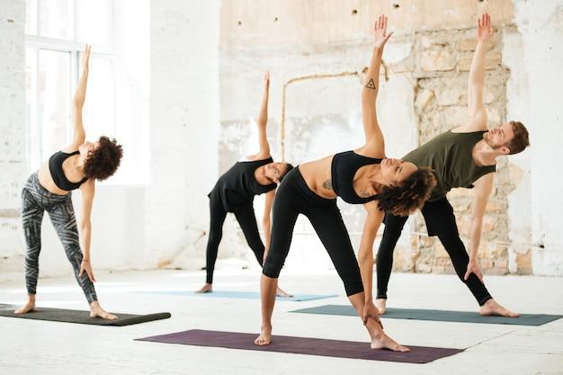 Bild der jungen leute, die yoga im fitnessstudio tun