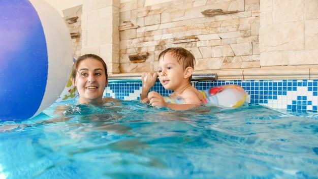 Bild der jungen mutter, die ihr kleines 3-jähriges jungenkind schwimmen lehrt und mit buntem strandball im hallenbad spielt