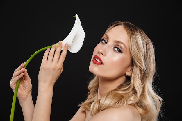 Bild der jungen schönen frau mit den roten lippen des hellen make-ups, die lokalisiert mit blume aufwerfen.