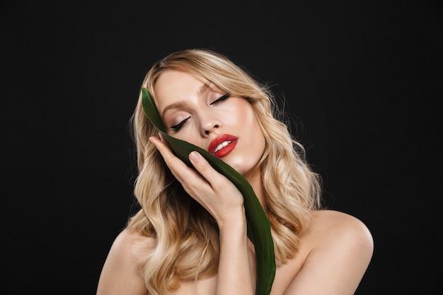 Bild der jungen schönen frau mit den roten lippen des hellen make-ups, die lokalisiert mit grüner blume des blattes aufwerfen.