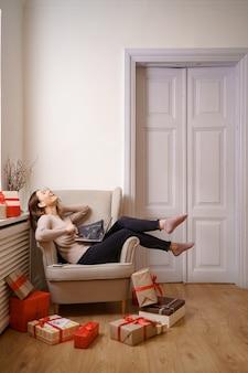 Bild der lachenden netten frau, die kreditkarte mit kopienraum unter verwendung des laptops hält, während auf sessel sitzt, der durch geschenkboxen am wohnzimmer umgeben ist