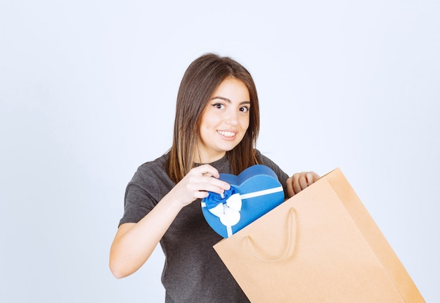 Bild der lächelnden frau, die ein herzförmiges geschenk in papiertüte steckt.