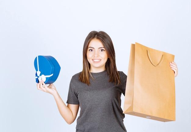 Bild der lächelnden frau, die ein herzförmiges geschenk und eine papiertüte in den händen hält.