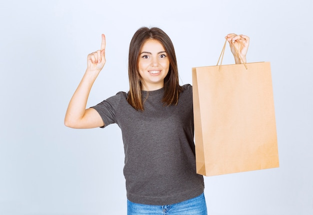 Bild der lächelnden frau, die eine papiertüte hält und mit einem zeigefinger nach oben zeigt.