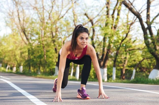 Bild der lächelnden hübschen sportfrau, die sich zum laufen vorbereitet