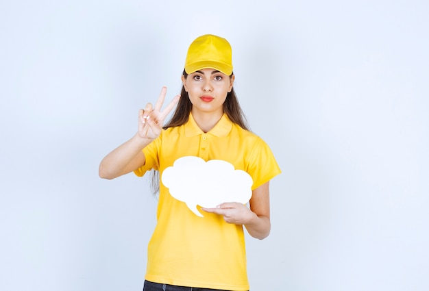 Bild der lieferfrau in gelber mütze, die mit sprechblase über weißer wand posiert.