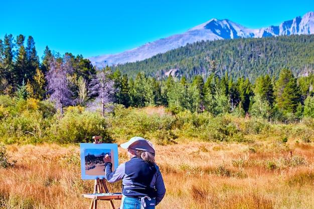 Bild der malerin außerhalb der wüstenmalereiszene der berglandschaft