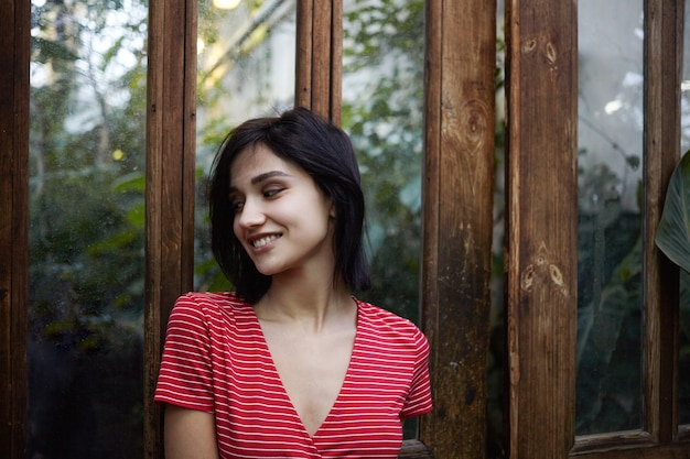 Bild der modischen jungen brünetten europäischen dame, die stilvolles rotes kleid mit weißen streifen trägt, die draußen an holztür mit gespiegelter oberfläche aufwerfen und mit positivem glücklichem lächeln wegschauen