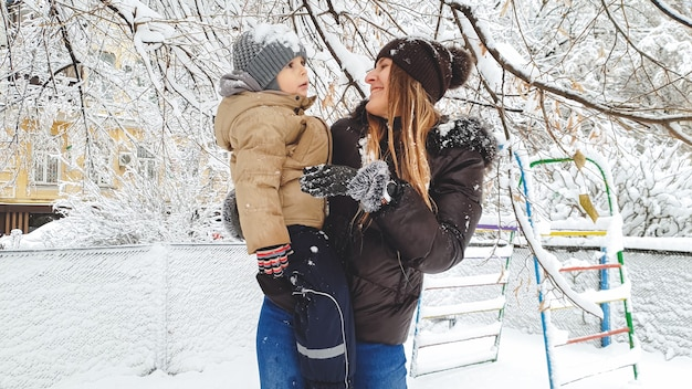 Bild der mutter mit ihrem sohn viel spaß beim spielen der schneebälle auf dem spielplatz im park