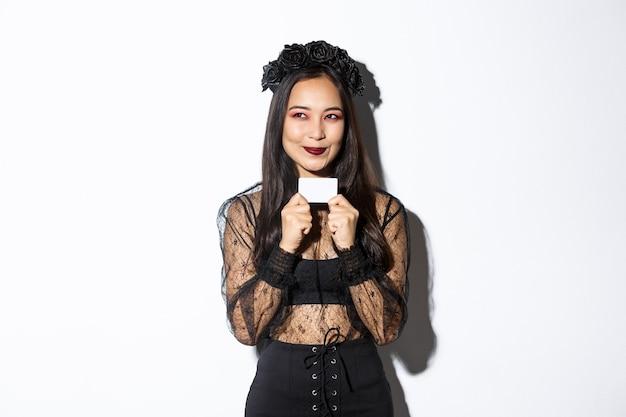 Bild der nachdenklichen asiatischen frau im schwarzen gotischen kleid haben einen plan, kreditkarte haltend, lächelnd erfreut an der oberen linken ecke.