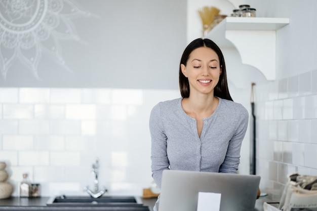 Bild der niedlichen brünetten frau, die auf dem tisch in der küche sitzt und laptop verwendet