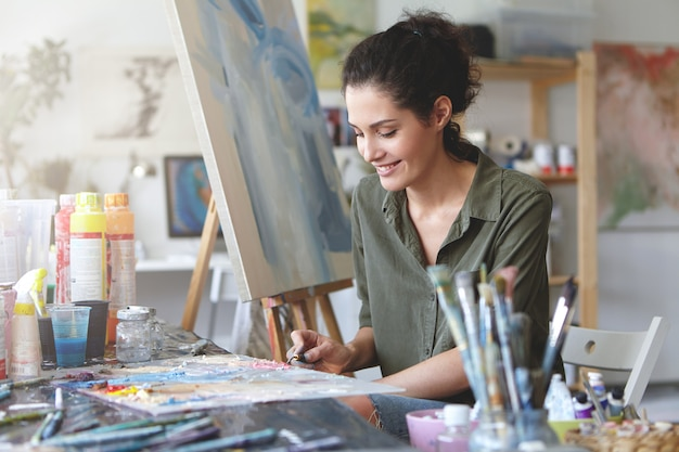Bild der niedlichen künstlerin, die am tisch sitzt, umgeben von aquarellen, etwas an der staffelei zeichnend, glücklichen ausdruck habend. brünette junge frau, die mit kreativer arbeit an werkstatt beschäftigt ist