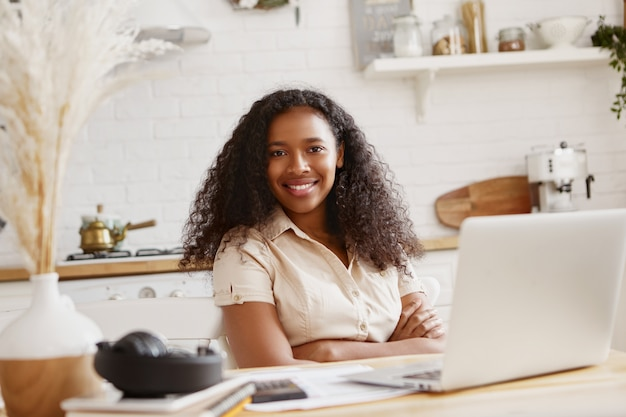 Bild der niedlichen stilvollen jungen afroamerikanischen buchhalterin mit zuversichtlichem zahnigem lächeln, das entfernt auf laptop-computer arbeitet und finanzen in der küche tut. technologie, beruf und freiberuflich tätig