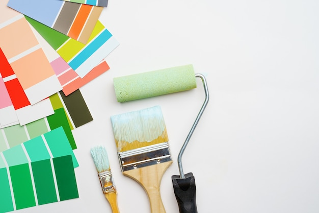 Bild der palette mit blauen und grünen farben, walze, bürsten auf leerem weißem hintergrund