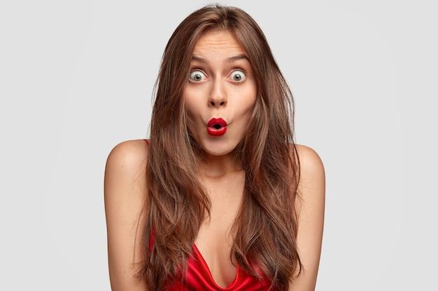 Bild der schockierten grünäugigen jungen frau hält mund rund, hat roten lippenstift