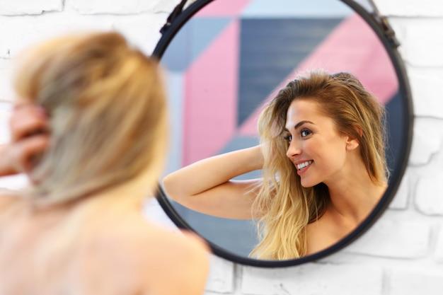 Bild der schönen blonden kaukasischen frau, die im badezimmer mit nassem haar aufwirft.