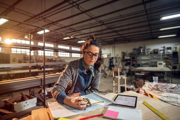 Bild der schönen fokussierten architektin mittleren alters in ihrer werkstatt, die an neuen projekten arbeitet.
