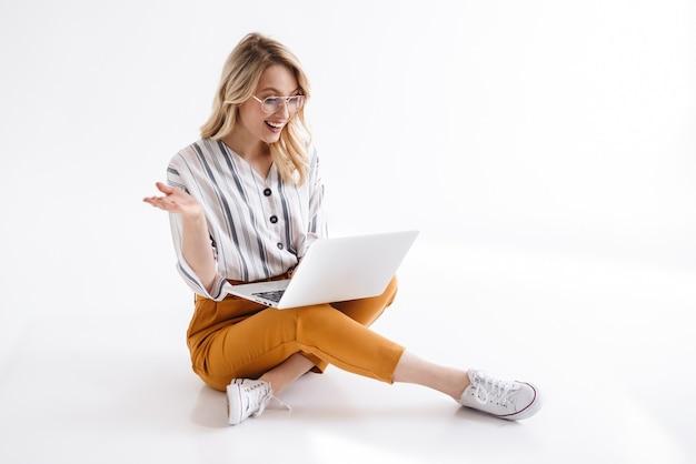 Bild der schönen frau, die brillen trägt, die lächeln und laptop betrachten, während auf dem boden lokalisiert über weißer wand sitzen